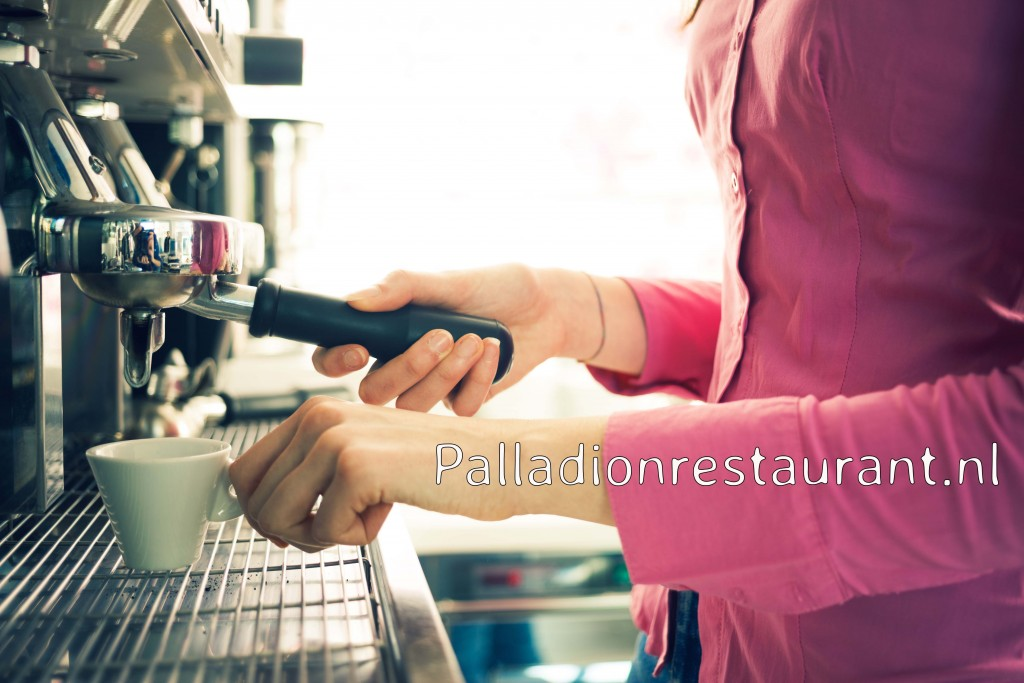 Young waitress making coffee with an espresso coffee machine, she is holding a cup and the filter holder